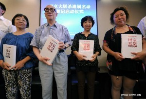 Yu Changxiang(2th L), victim and survivor of Nanjing Massacre, and his three daughters receive data sets about the massacre during the launching ceremony of a project to register victims of Nanjing Massacre, in Nanjing, capital of east China's Jiangsu Province, July 6, 2014. The Memorial Hall of the Victims in Nanjing Massacre by Japanese Invaders officially began to register the victims in massacre on Sunday.